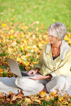 Full length of senior woman using laptop while sitting in park photo