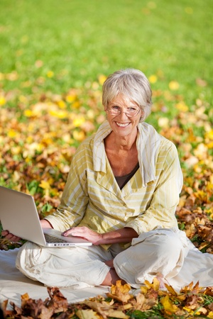 crossed legs: Senior woman using laptop while sitting in park