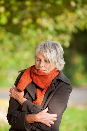 tremble: Senior woman with eyes closed shivering in park