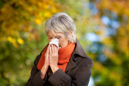 sneeze: Senior woman in jacket suffering from cold in park