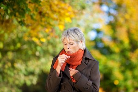 tos: Mujer mayor en el sufrimiento de la chaqueta de la tos en el parque