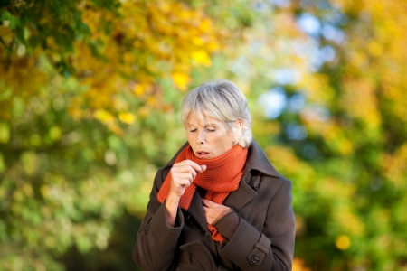 coughing: Senior woman in jacket suffering from cough in park