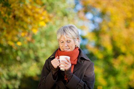 Senior woman in jacket enjoying coffee in park photo