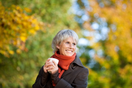 old lady: Smiling senior woman in jacket enjoying coffee in park Stock Photo