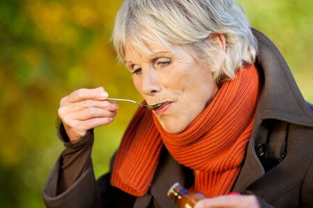 Senior woman in jacket drinking cough syrup at park Stock Photo - 21246812