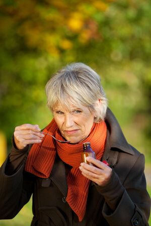 Senior woman in jacket with cough syrup at park Stock Photo - 21246814