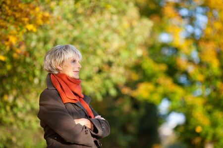 thoughtful woman: Thoughtful senior woman in jacket with arms crossed looking away in park