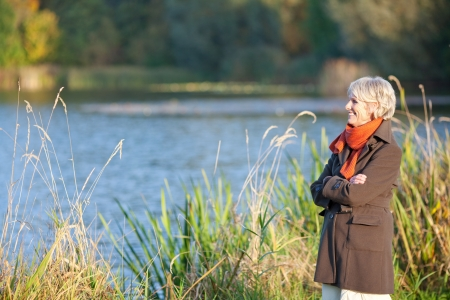 Happy senior woman enjoying sunlight at lake photo