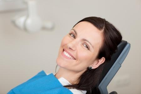 Portret van medio volwassen vrouwelijke patiënt lachend in de tandheelkunde