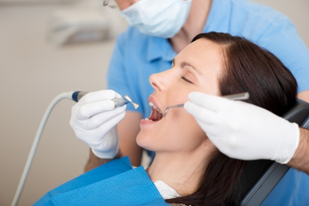 dentition: Mature dentist examining female patients mouth in clinic Stock Photo