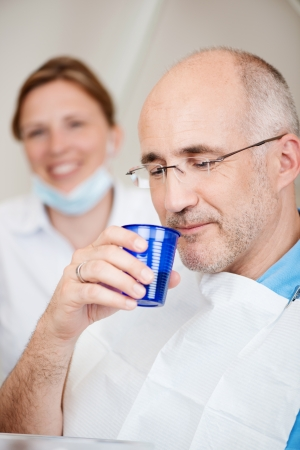 rinsing: Male patient rinsing mouth with dentist in background at clinic