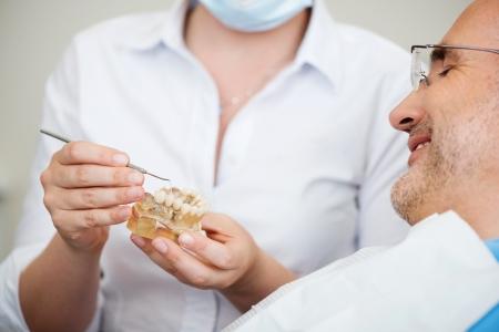 protease: Secci�n media de mujer dentista explicar dientes artificiales con el paciente en la cl�nica Foto de archivo
