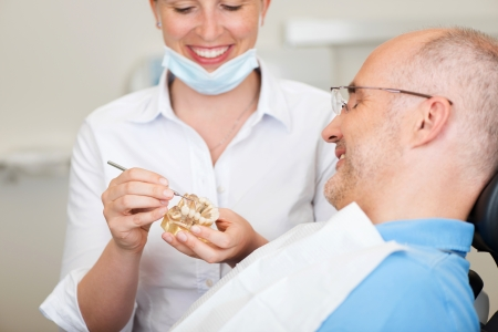 implants: Smiling female dentist explaining artificial teeth to patient in clinic