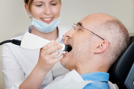 oral: Female dentist with dental camera examining patients teeth at clinic Stock Photo