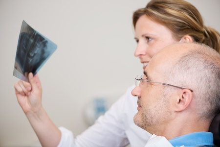 dental office: Female dentist and patient examining Xray in clinic Stock Photo