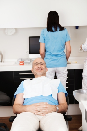 Cheerful patient in the dentists chair in dental studio photo