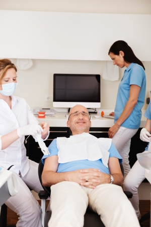 Male patient reclining on dental chair while dentist and assistants preparing for checkup in clinic photo