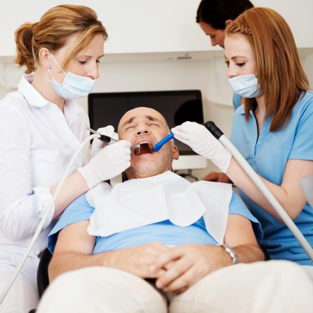 sucker: Female dentists using dental drill and sucker while examining mans mouth in clinic Stock Photo