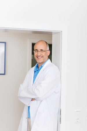 Portrait of confident male dentist with arms crossed standing at doorway in clinic photo