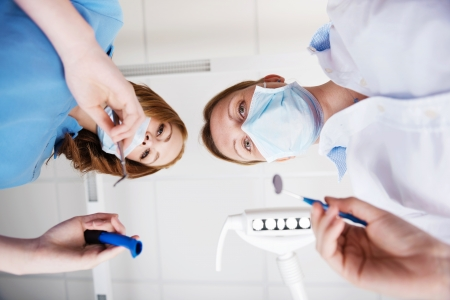 dentist mask: Directly below view of female dentists using dental tools in clinic