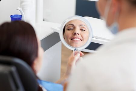 tooth cleaning: Patient admires dentists work in a mirror