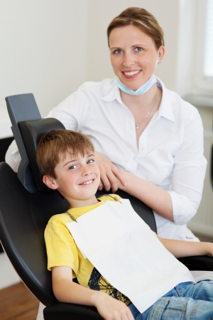 Smiling boy sitting in a dentists chair and smiling dentist photo