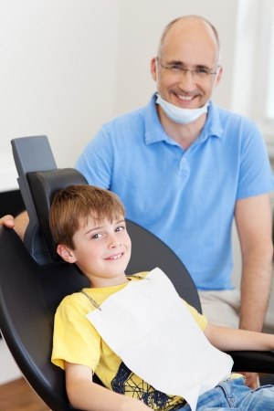 masks: Portrait of mature dentist with little male patient smiling in clinic Stock Photo
