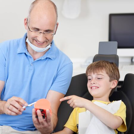 dentalcare: Dentist gives a dentalcare prevention lesson to a boy Stock Photo