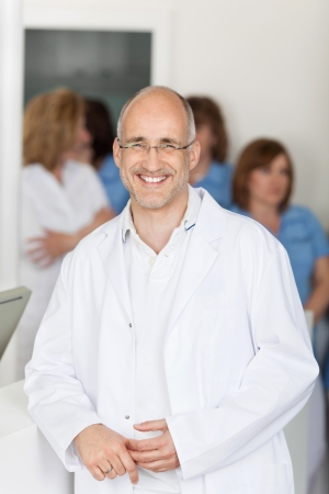 Portrait of male dentist smiling with assistants in background at clinic photo