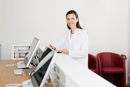recepcionista: Doctor sonriente mujer de pie en el mostrador de recepción Foto de archivo