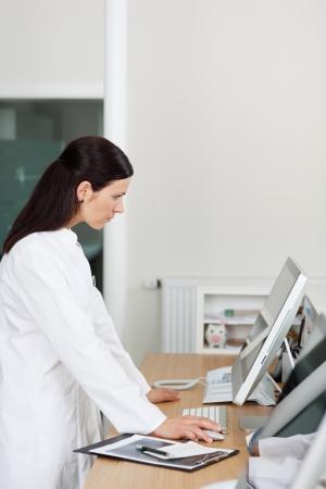 personal medico: Femal�e m�dico mira a su escritorio de la computadora