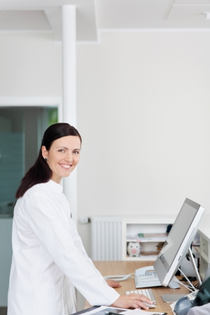 Portrait of confident mid adult receptionist at reception counter in dentists clinic photo
