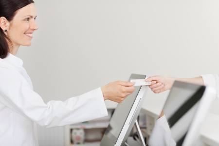 Side view of mid adult female receptionist receiving card from patient in dentist clinic