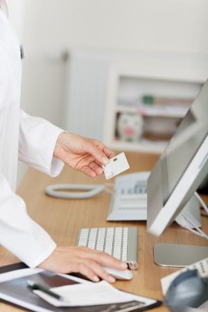 administrativo: Imagen cosechada de la recepcionista que sostiene la tarjeta ID, mientras que usando la computadora en el mostrador de recepci�n en la cl�nica del dentista
