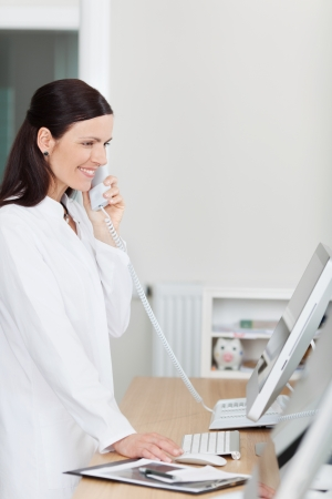 Female receptionist using landline phone at reception counter in dentists clinic photo