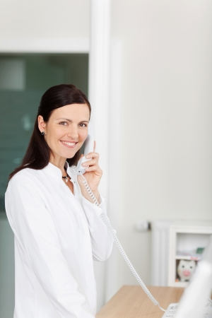 Female medical assistant talking on a telephone photo