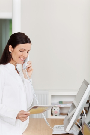answering call: Female medical assistant answers phone call at reception