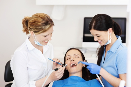 Happy female dentists examining patients mouth with tools in clinic photo