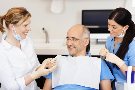 prosthetics: Dentist explaining teeth model to male patient at clinic Stock Photo