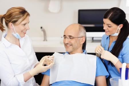 Dentiste expliquant modèle de dents au patient de sexe masculin à la clinique Banque d'images - 21246880
