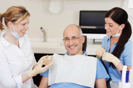 prosthetics: Dentist explaining teeth model to smiling male patient at clinic