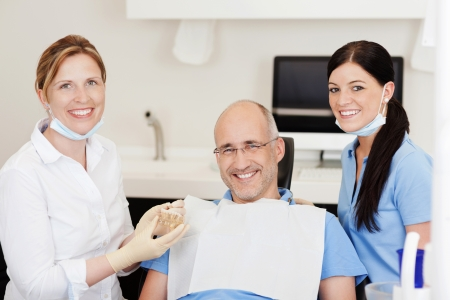 dentistry: Dentist explaining teeth model to male patient at clinic while looking at camera