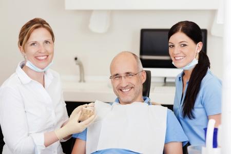 Tandarts die tanden model aan mannelijke patiënt in de kliniek, terwijl kijken naar de camera
