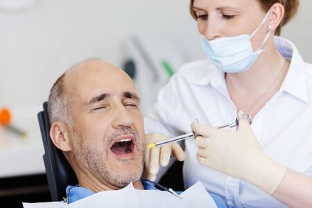 anesthetize: Female dentist injecting anesthesia to male patient before treatment in clinic Stock Photo