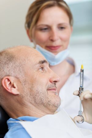 dental fear: Female dentist injecting anesthesia to patient before treatment Stock Photo