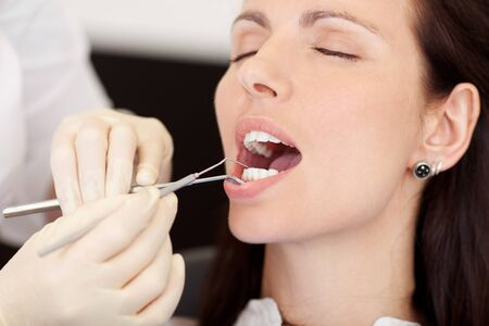 mouth closed: closeup of pretty female patient receiving treatment from dentist at clinic Stock Photo