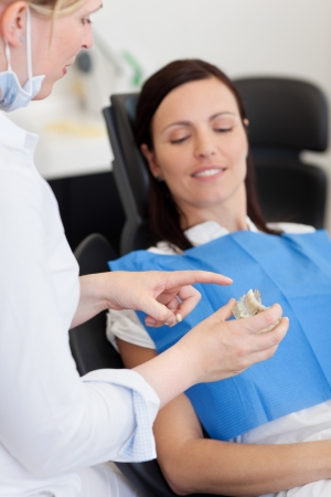 Closeup of dentist explaining teeth model to female patient at clinic
