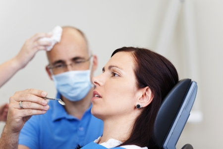 dental fear: Close-up of an female anxious patient at the dentist Stock Photo
