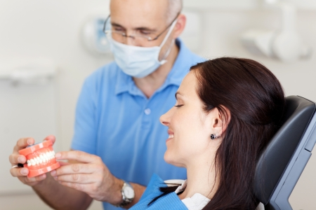 Male dentist explaining artificial teeth to patient in clinic Stock Photo - 21246952