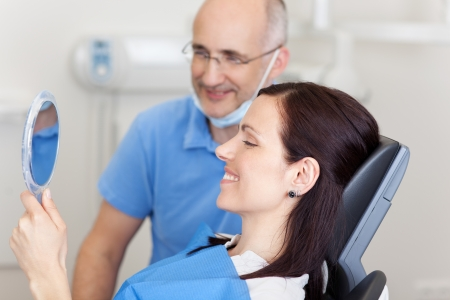 orthodontics: Happy mid adult female patient with doctor looking at mirror in clinic